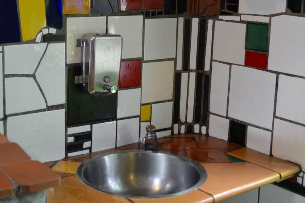 Hundertwasser's style can be be seen in every part of the toilets. Here, the wash basin with colourful wall tiles.