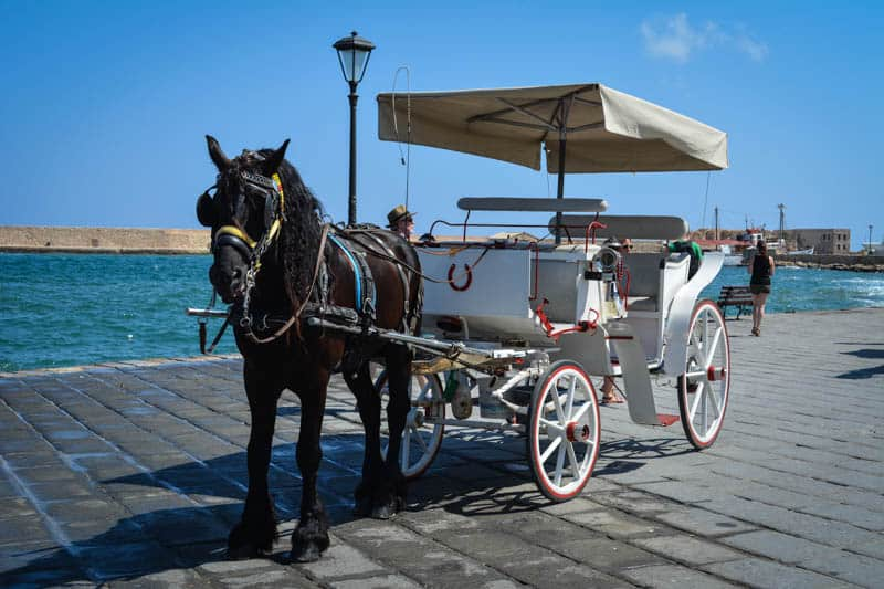 Horse drawn carriages are waiting around the Venetian Harbour. One of the things visitors can try when visiting this Cretan city.