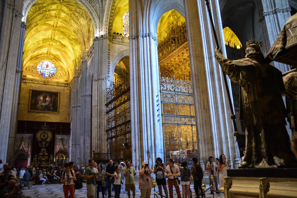 Visitors inside Seville Cathedral take pictures of Christopher Columbus' tomb. Another great reason to visit is the over dimensional golden altarpiece as well as the views from the bell town, the Giralda.
