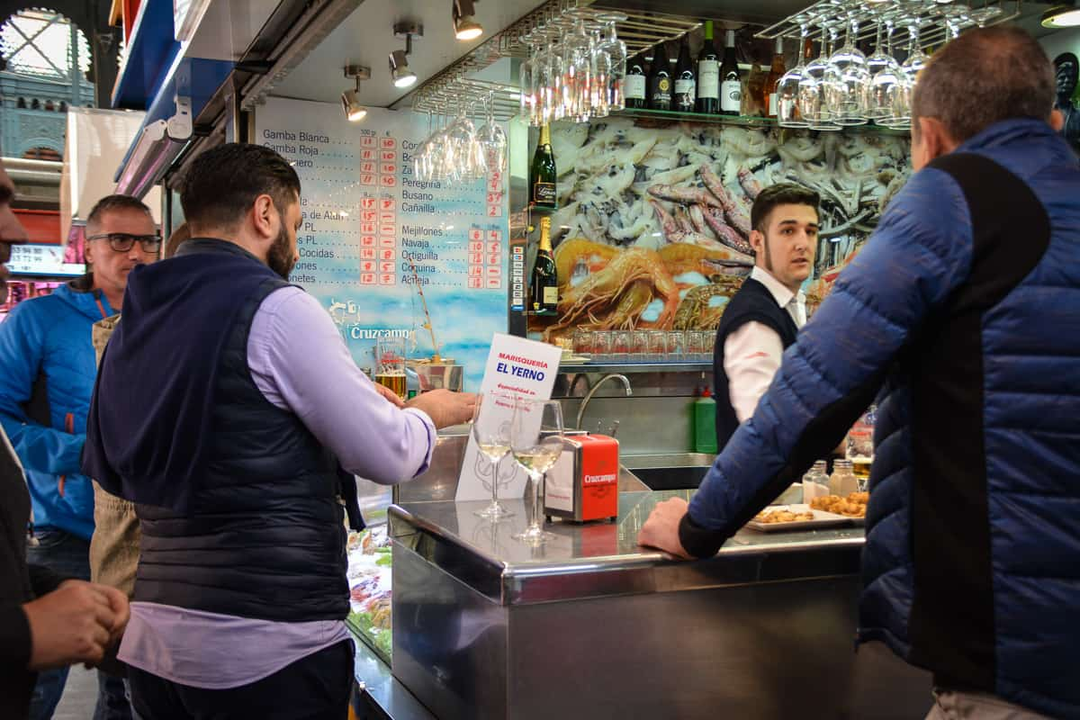 Customers order tapas at one of the handful of bars inside the Malaga market hall.