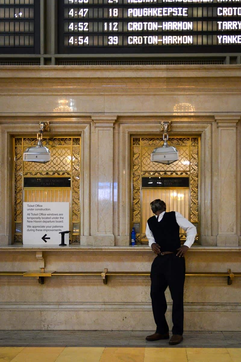 Man leaning against the historic train ticket counters at Grand Central Station.
