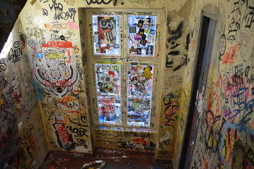 The staircase of Haus Schwarzenberg is a mess of scribbled tags and stickers.