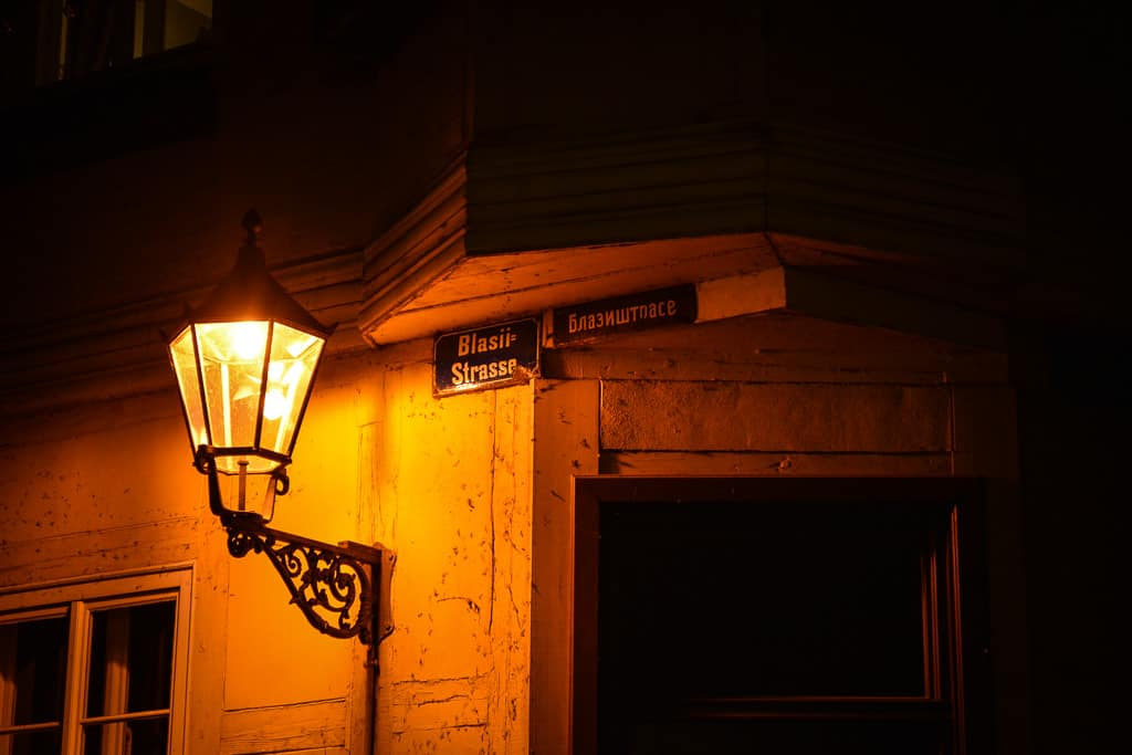Darkness and golden light add mystery and charm to the ancient city streets.
