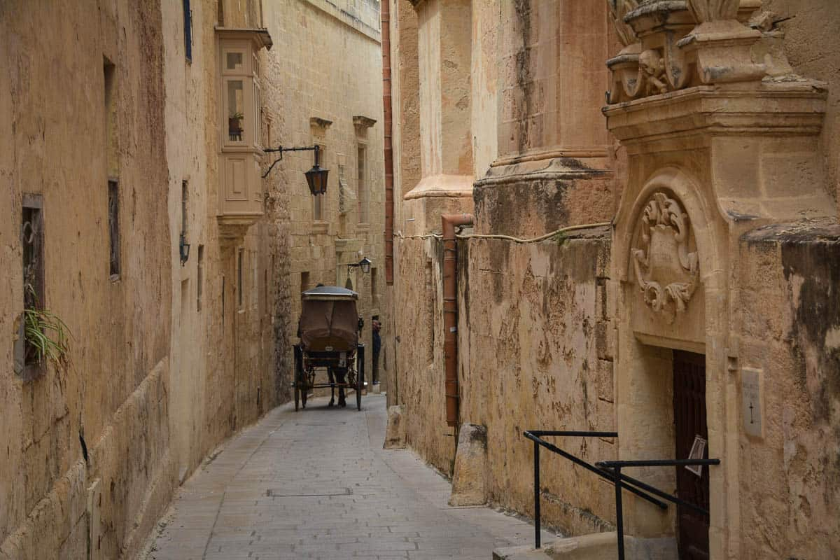 Some city streets in Malta and Gozo like this one in Mdina are so narrow that not even a normal sized horse carriage would fit. Driving in Malta therefore requires some negotiation skills.